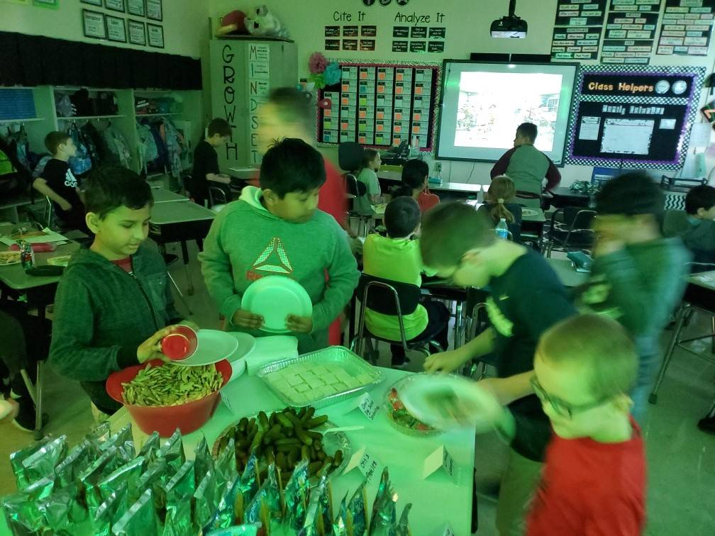 Students getting pickles from a table.