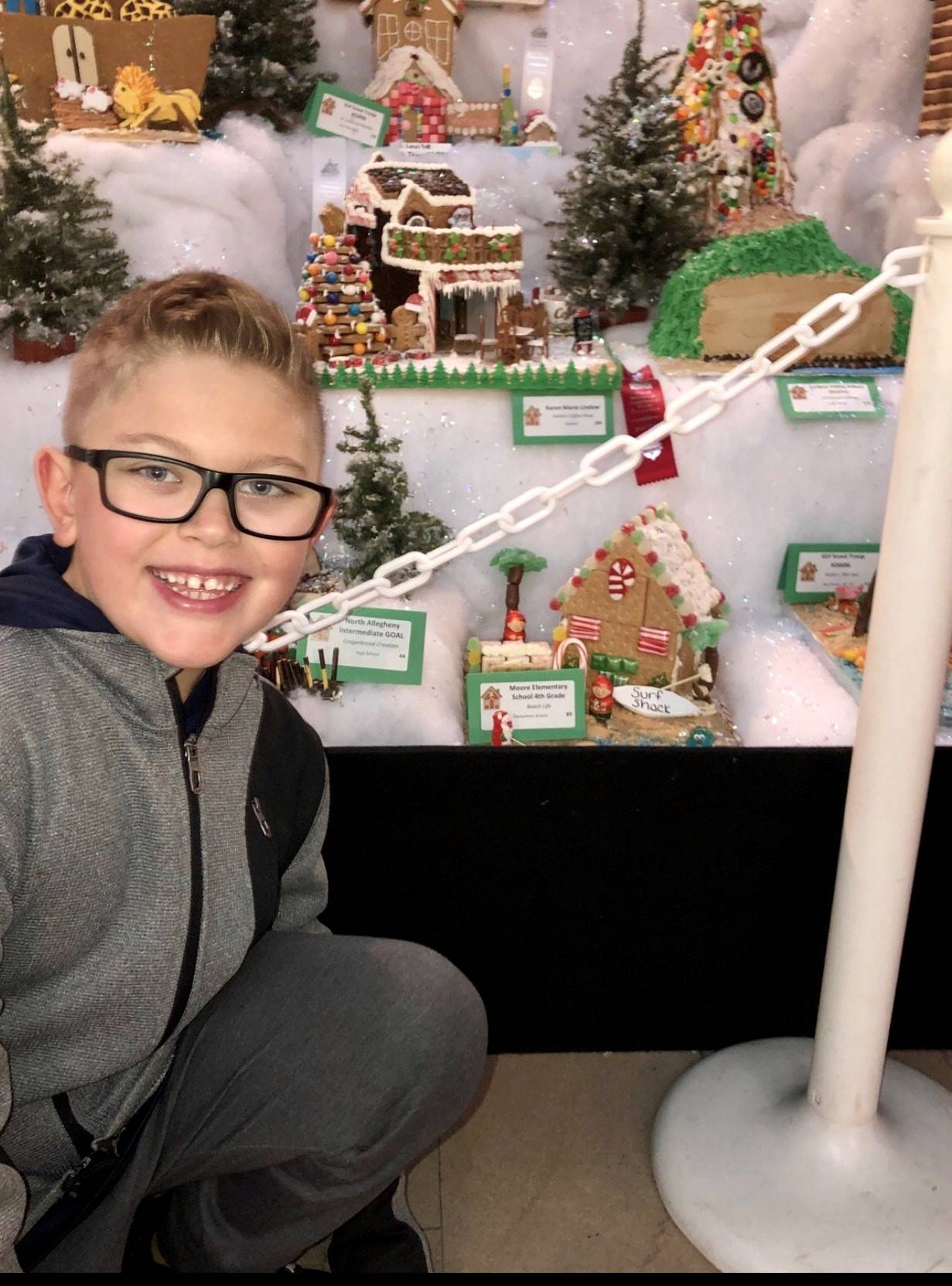 Student in front of gingerbread house.