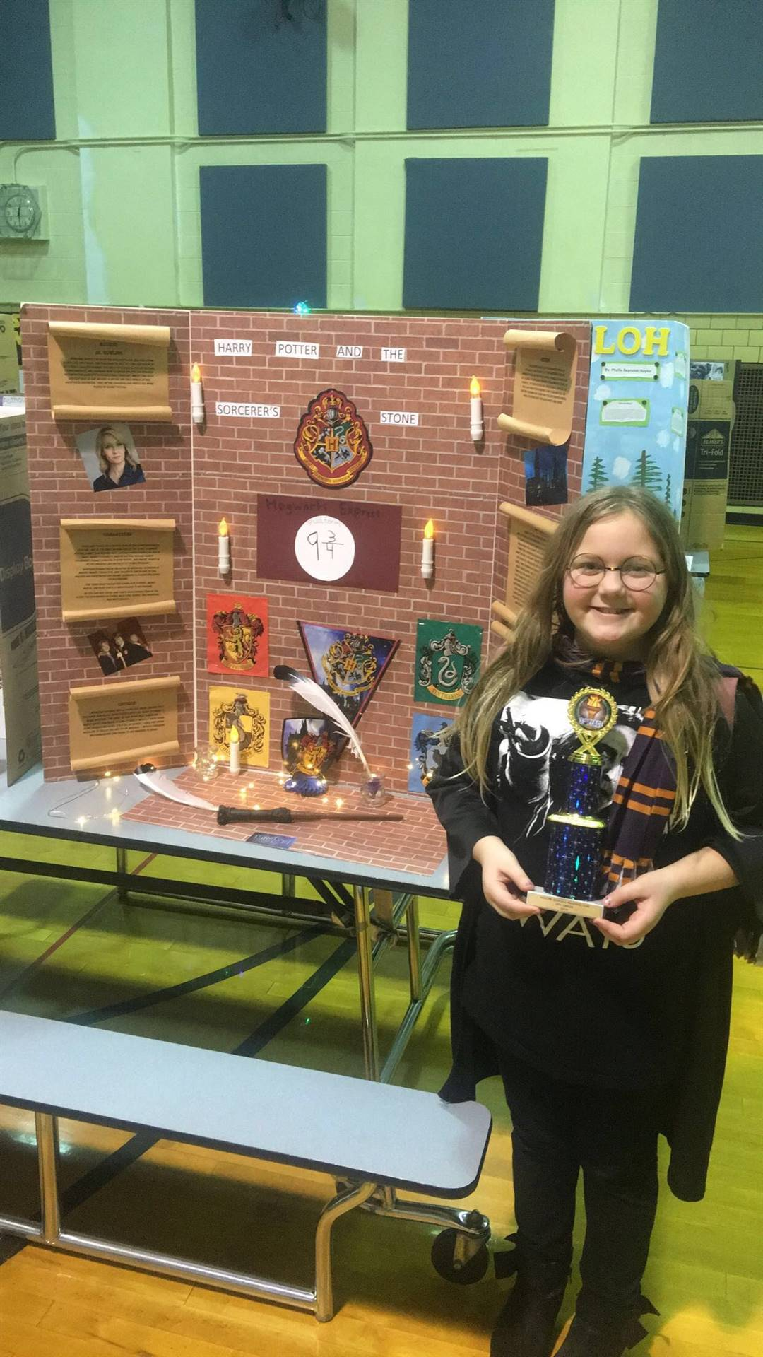 Student that placed in the reading fair with their trophy and poster.