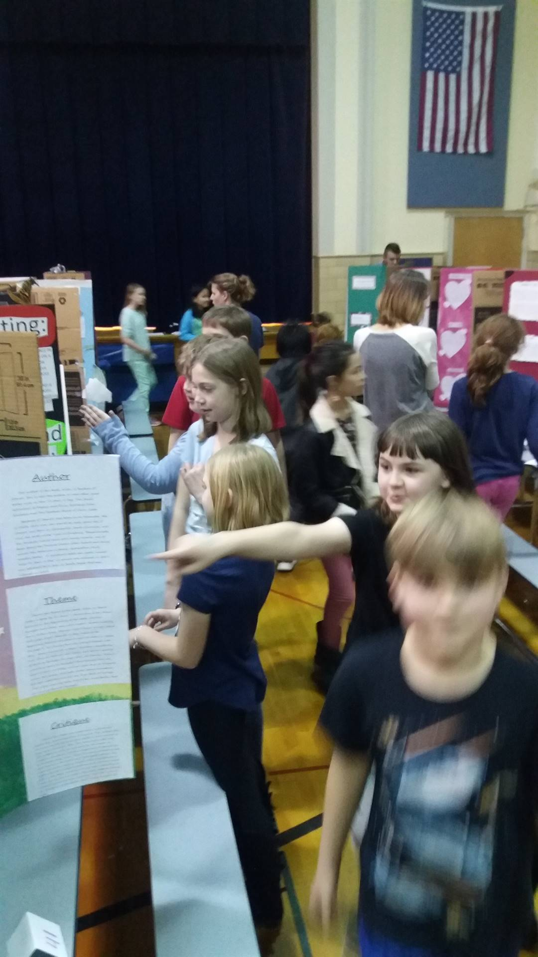Students looking at reading fair poster boards.