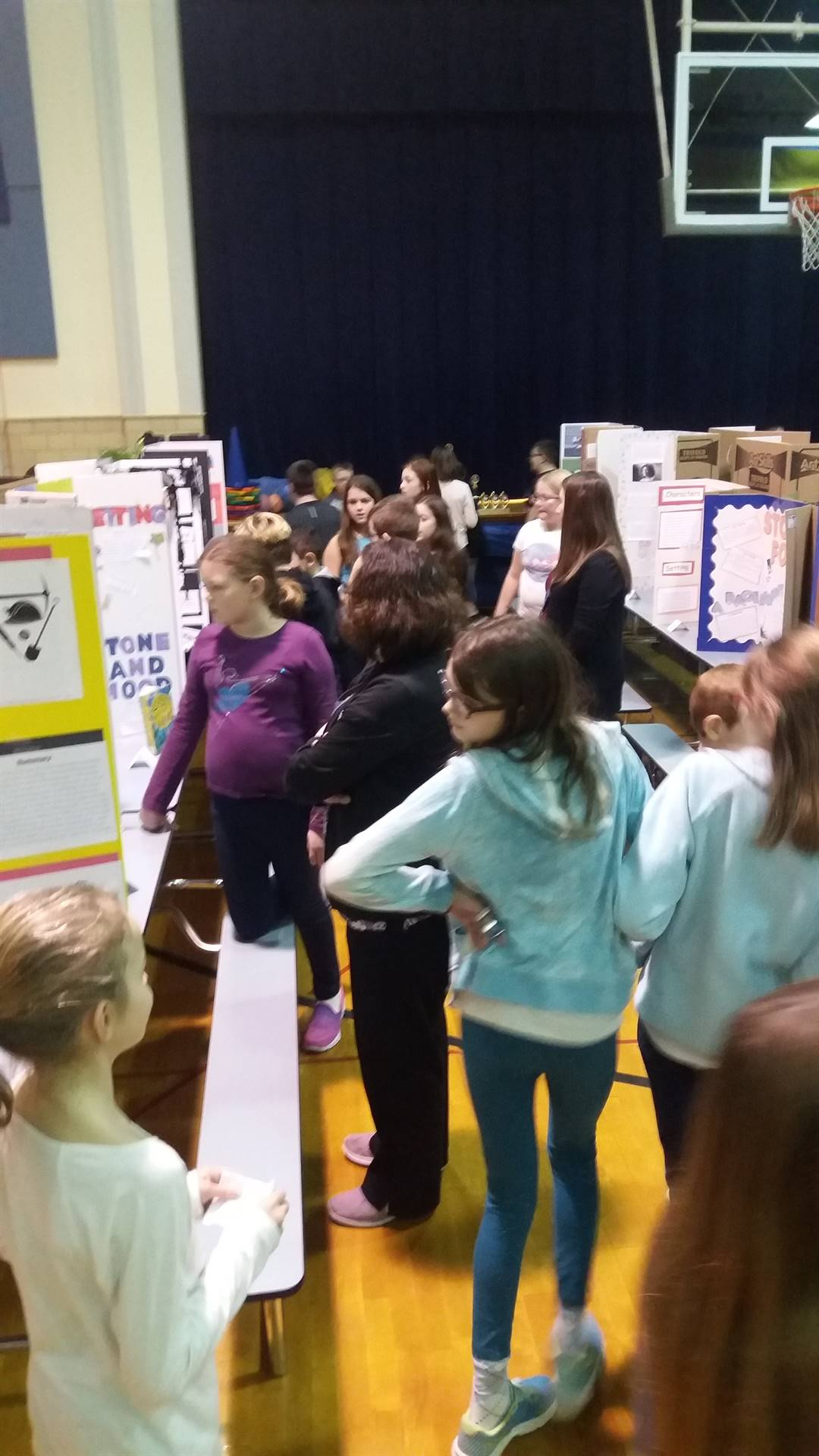 Students looking at reading fair posters in the gym.