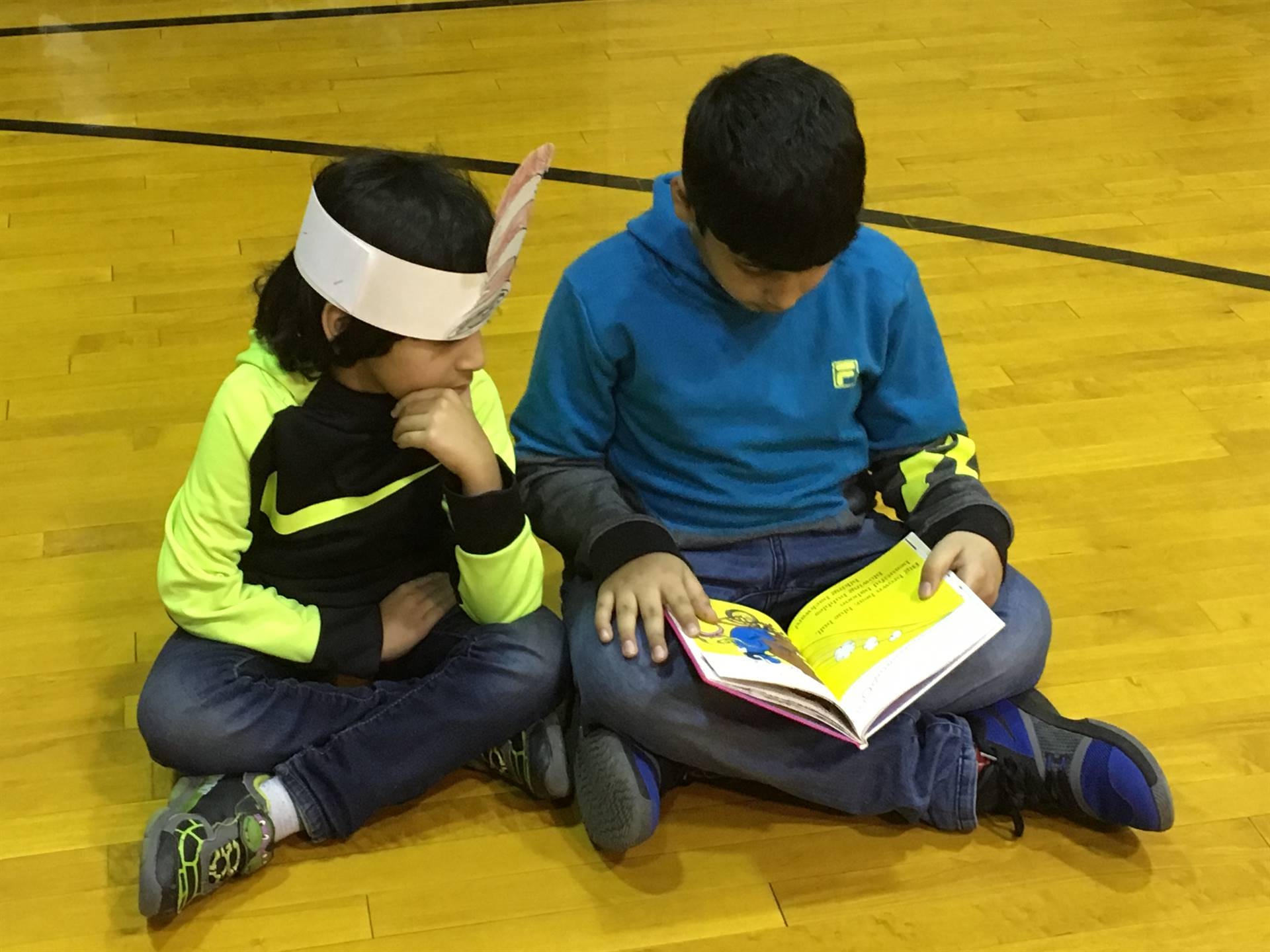 A student reading to a younger student.